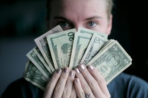 Get financed with small business loans with bad credit. Woman holding cash.
